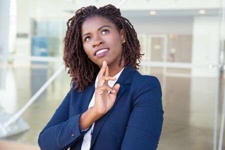 Pensive smiling professional thinking outside. Young black business woman standing at outdoor glass wall, touching chin and looking up. Thinking concept