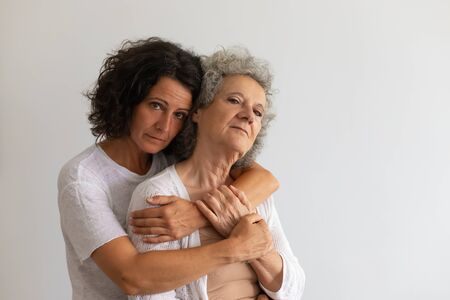 Serious adult daughter and senior mother posing in studio. Middle aged woman hugging elderly lady and looking at camera. Mother and daughter portrait concept Stockfoto