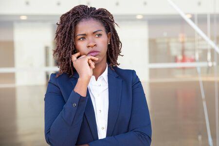 Focused pensive leader thinking outside. Serious young black business woman standing at outdoor glass wall, touching chin and looking away into distance. Thinking concept