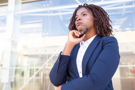 Pensive serious professional waiting colleague outside. Young African American business woman standing at outdoor glass wall, touching chin and looking into distance. Professional outside concept Stockfoto