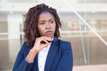 Pensive office employee thinking outside. Serious young African American business woman standing at outdoor glass wall, touching chin and looking away into distance. Thinking concept