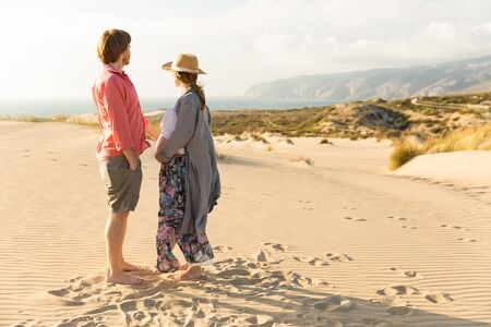 Happy young couple standing on sand during summer vacation. Full length portrait of husband and pregnant wife looking at distance. Pregnancy concept Stock fotó