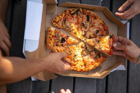 Cropped shot of friends eating pizza. Selective focus of young people eating delicious pizza outdoors. Take away food concept
