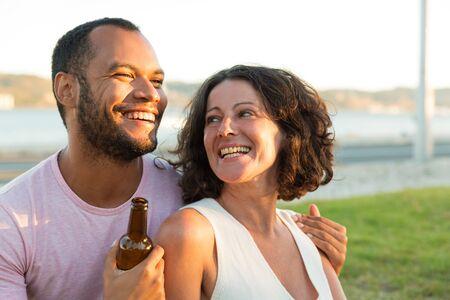 Feliz pareja relajada bebiendo cerveza y charlando al aire libre. Hombre y mujer sentados en la hierba, abrazándose, sosteniendo una botella de cerveza y riendo. Concepto de citas al aire libre Foto de archivo