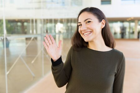 Friendly happy Latin woman waving hello. Young woman in casual posing indoors with glass wall interior in background. Greeting or communication concept Stockfoto