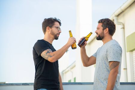Two male friends sharing good news and drinking beer on outdoor terrace. Two young men in casual meeting outside. Friendly communication concept