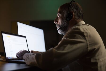 Serious businessman in headset using laptop. Side view of focused mature male call center operator in headset working with computer in dark office. Customer support concept