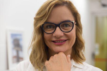 Überzeugte Geschäftsfrau, die in die Kamera lächelt. Nahaufnahmeporträt der schönen Geschäftsfrau mittleren Alters mit Brille, die mit der Hand am Kinn steht und in die Kamera lächelt. Geschäftskonzept