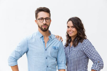 Friendly attractive couple posing together. Young woman in casual and man in glasses standing isolated over white background. Relationship and unity concept Stock Photo