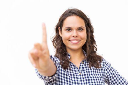 Gelukkig vrolijk studentenmeisje wat betreft glasraad met vinger. Jonge vrouw in casual gecontroleerd overhemd staande geïsoleerd op witte achtergrond. Reclame- of technologieconcept