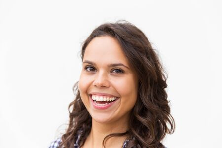 Closeup of broadly smiling student girl with white healthy teeth. Young woman in casual checked shirt standing isolated over white background. Female portrait concept