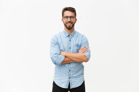 Happy laughing guy posing with arms folded. Handsome young man in casual shirt and glasses standing isolated over white background. Male portrait concept Фото со стока