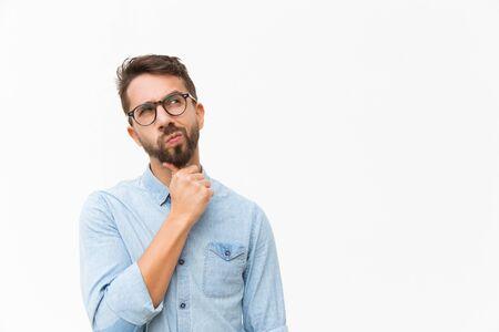 Client masculin réfléchi, pensant fort, regardant l'espace de copie, penché le menton à portée de main. Beau jeune homme en chemise décontractée et lunettes debout isolé sur fond blanc. Concept d'offre spéciale Banque d'images