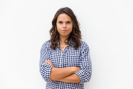 Positive determined student girl with arms crossed and funny grimace looking at camera. Young woman in casual checked shirt standing isolated over white background. Human emotion concept