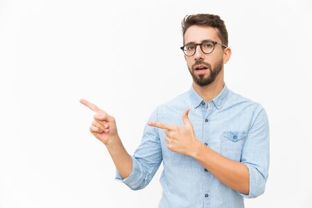 Serious surprised male customer presenting copy space, pointing fingers away. Handsome young man in casual shirt and glasses standing isolated over white background. Advertising concept