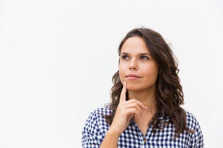 Une cliente rêveuse et pensive touchant le menton avec le doigt et regardant loin l'espace de copie. Jeune femme en chemise à carreaux décontractée debout isolé sur fond blanc. Concept publicitaire Banque d'images