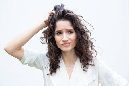 Femme pensive inquiète se grattant la tête et détournant les yeux. Jeune femme aux cheveux ondulés en chemise décontractée debout isolé sur fond blanc. Concept de prise de décision difficile