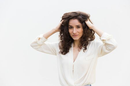 Happy positive woman setting curly hair with fingers, massaging head skin. Wavy haired young woman in casual shirt standing isolated over white background. Beauty care concept