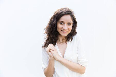 Fille étudiante mignonne positive avec les mains jointes souriant à la caméra. Jeune femme aux cheveux ondulés en chemise décontractée debout isolé sur fond blanc. Concept de portrait de jeune femme