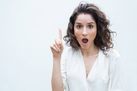 Excited woman gasping, pointing finger up, staring at camera with open mouth. Wavy haired young woman in casual shirt standing isolated over white background. Advertising concept