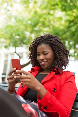 Cheerful woman using smartphone on street. Beautiful smiling young African American woman sitting on bench and using mobile phone. Technology concept