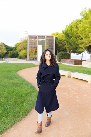 Serious pensive beautiful student girl enjoying walking in park. Wavy haired young woman in casual overcoat posing outside. Weekend in park concept