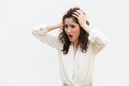Shocked disappointed woman gasping, holding head and staring away at copy space. Wavy haired young woman in casual shirt standing isolated over white background. Mistake or stress concept