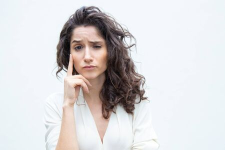 Pensive woman touching face with finger, looking at camera, thinking hard. Wavy haired young woman in casual shirt standing isolated over white background. Decision making concept Banque d'images