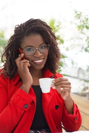 Woman with coffee and smartphone smiling at camera. Beautiful happy young African American woman holding cup of coffee, talking by cell phone and smiling at camera in cafe. Connection concept