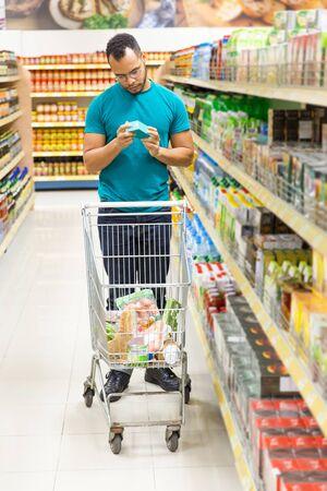 Nachdenklicher afroamerikanischer Mann, der im Lebensmittelgeschäft einkauft. Ernster junger Kunde, der im Gang steht und Waren auswählt. Shopping-Konzept Standard-Bild
