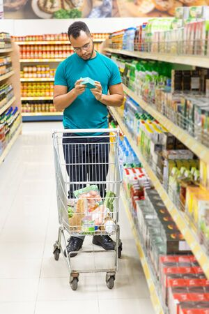 Thoughtful African American man shopping at grocery store. Serious young customer standing in aisle and choosing goods. Shopping concept Reklamní fotografie
