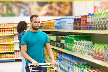 Serious African American man walking with shopping cart. Focused young man in eyeglasses making purchases in supermarket. Shopping concept