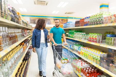 Front view of young couple shopping at grocery store. Focused people talking while walking in aisle with alcohol drinks. Shopping concept