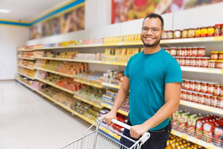Smiling African American man posing with shopping cart. Cheerful bearded guy standing in aisle and looking at camera. Shopping concept 免版税图像
