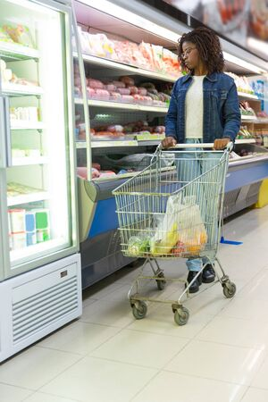 Young black woman choosing food in grocery store, wheeling cart, looking at shelves. Buyer shopping in supermarket. Buying products concept
