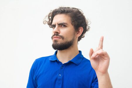 Serious strict guy making warning gesture, pointing index finger up. Handsome bearded young man in blue casual t-shirt posing isolated over white background. Attention or caution concept