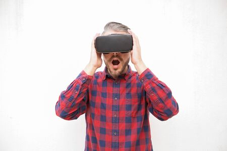 Shocked bearded man in VR headset. Excited man with open mouth using virtual reality headset on grey background. Technology concept