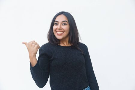 Happy joyful woman pointing thumb away. Beautiful young woman in casual sweater posing isolated over white background. Advertising concept