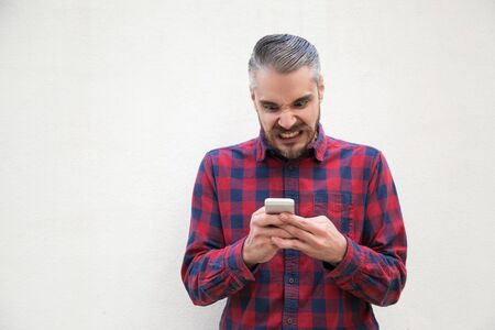 Irritated man using mobile phone. Font view of angry middle aged man texting via smartphone on grey background. Technology and emotion concept