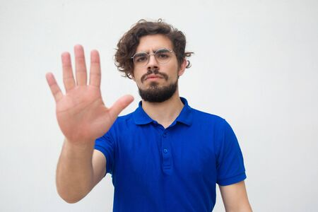 Serious strict guy making hand stop gesture. Handsome bearded young man in blue casual t-shirt posing isolated over white background. Warning or prohibition concept