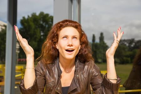 Smiling sarcastic woman sitting in outdoor coffee shop, rolling eyes, gesturing. Red curly haired young woman in casual posing in cafe. Sarcasm or relief concept