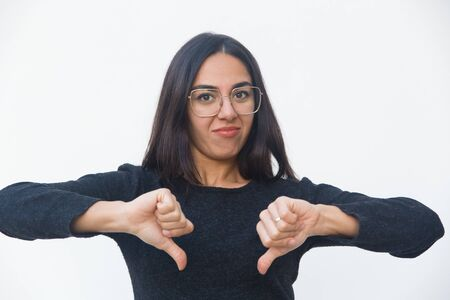Skeptical dissatisfied customer showing thumbs down, making dislike gesture. Beautiful young woman in casual sweater posing isolated over white background. Negative feedback concept
