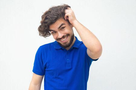 Pensive embarrassed guy scratching head, feeling guilty, justifying himself. Handsome bearded young man in blue casual t-shirt posing isolated over white background. Cheating concept