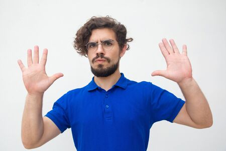 Concerned guy showing palms, hands, making surrender gesture. Handsome bearded young man in blue casual t-shirt posing isolated over white background. Calm down gesture concept