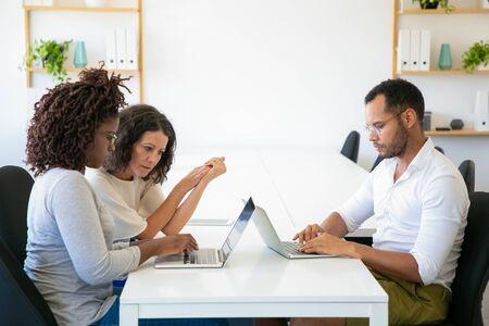 Sviluppatori premurosi che lavorano con il laptop. Concentrato giovane donna e uomo che digita sul computer portatile mentre è seduto in ufficio. Concetto di tecnologia