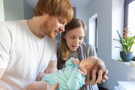 Nieuwe moeder en vader houden en knuffelen baby in de armen. Familieportret van paar en schattig klein kind in interieur. Gelukkig ouderschap concept Stockfoto