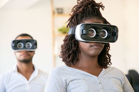 Two young programmers setting VR headset. Focused workers testing new device. Technology concept Banque d'images