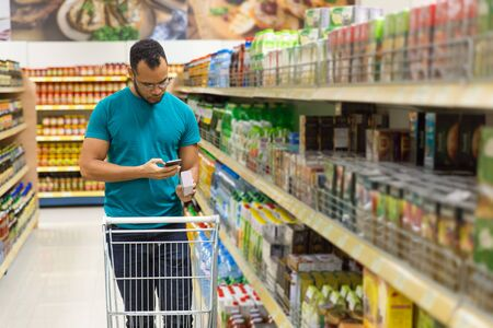 Focused African American man reading shopping list on smartphone. Responsible bearded guy buying food according to list. Shopping concept