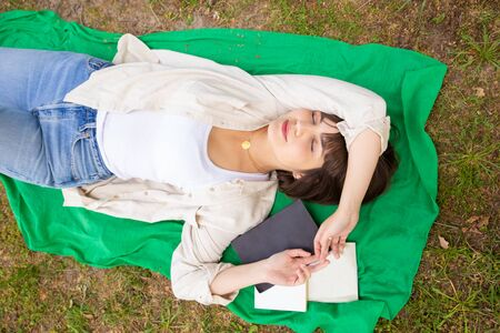 Female student sleeping with books in park. Top view of beautiful young woman lying on meadow with books and textbooks during daytime. Education concept