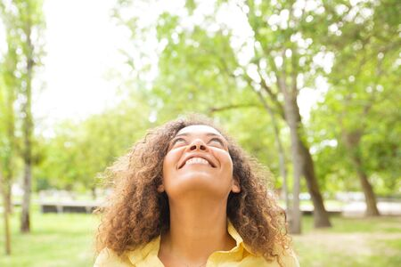 Positive carefree woman enjoying leisure time in park, looking up at copy space. Curly haired black woman in casual posing outdoors. Advertising concept